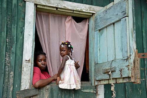 Mujer e hija en ventana en República Dominicana