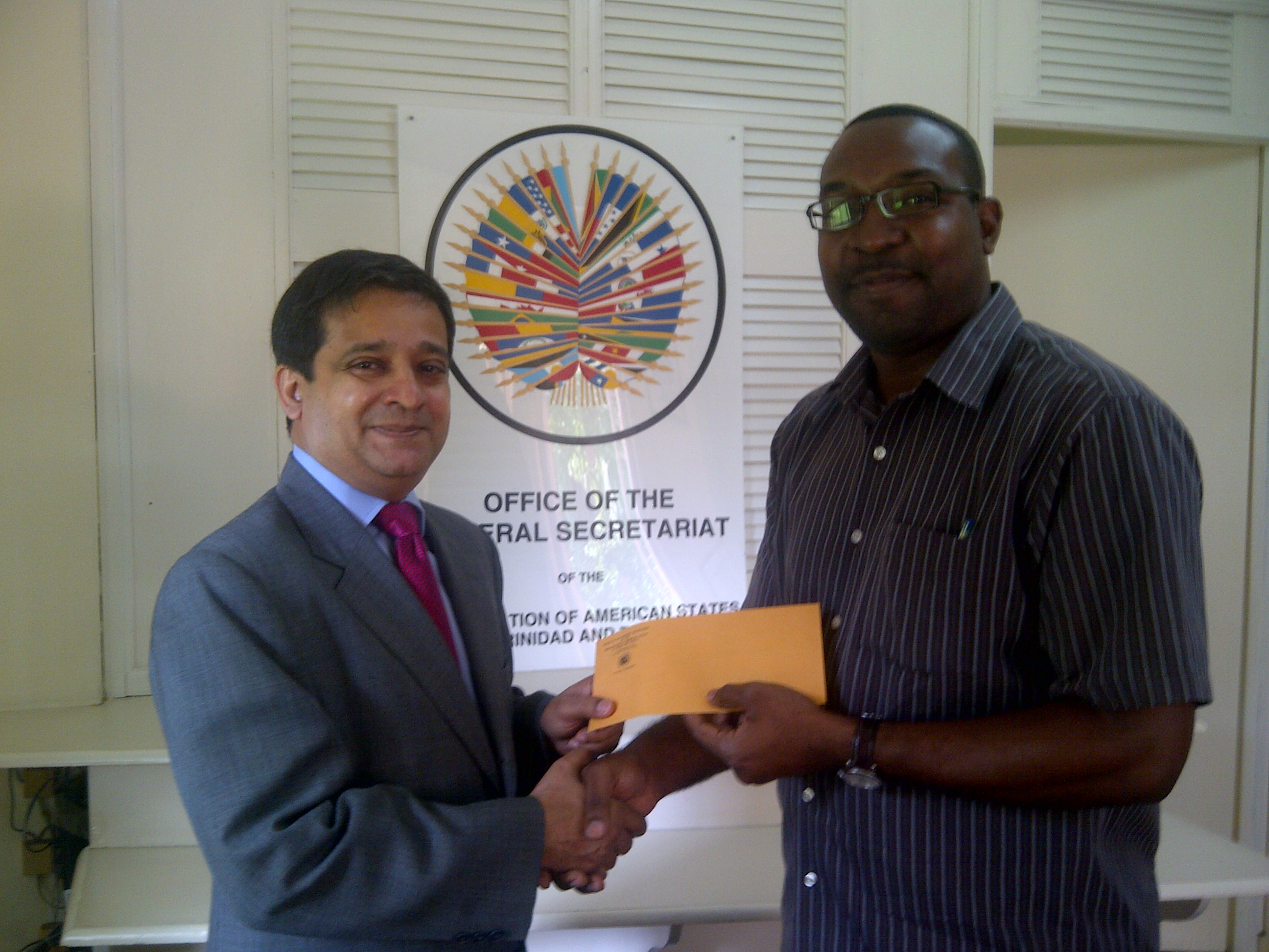 Dr. Riyad Insanally presents to Burton Hill the Association of Caribbean Nationals donation to the John Hayes Memorial Kidney Foundation in the name of Domingo Hill father of OAS staff member, Sheridon Hill